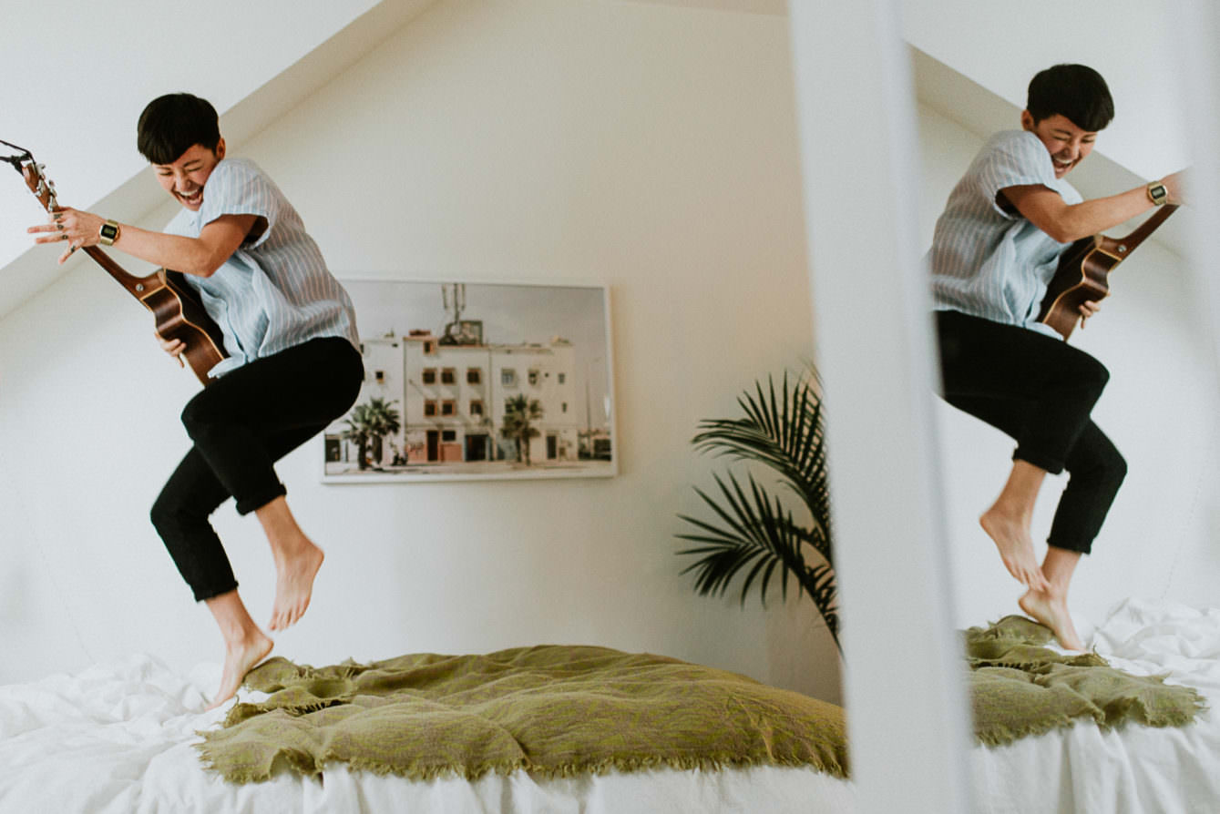 photo of musician Jody Mark Okabe jumping on bed playing ukulele by Vancouver portrait photographer Ronnie Lee Hill