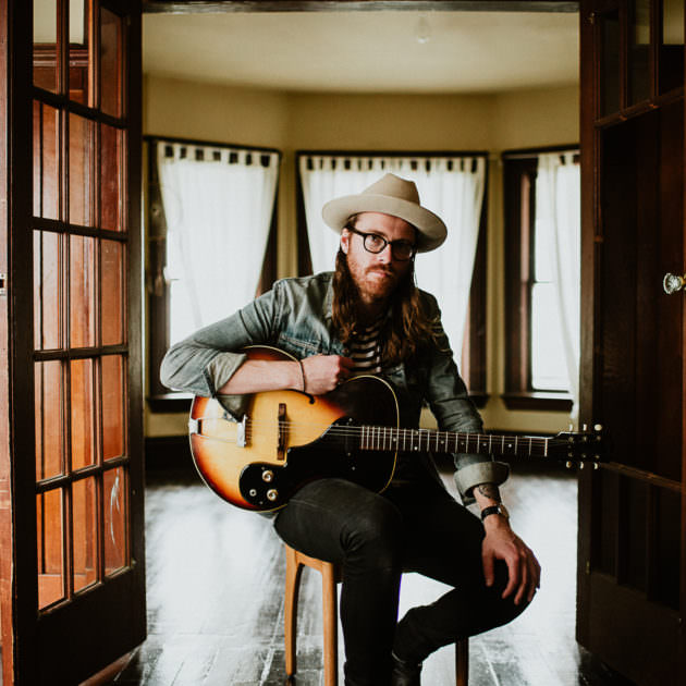 portrait of musician Matt Kelly in living room with guitar by photographer Ronnie Lee Hill