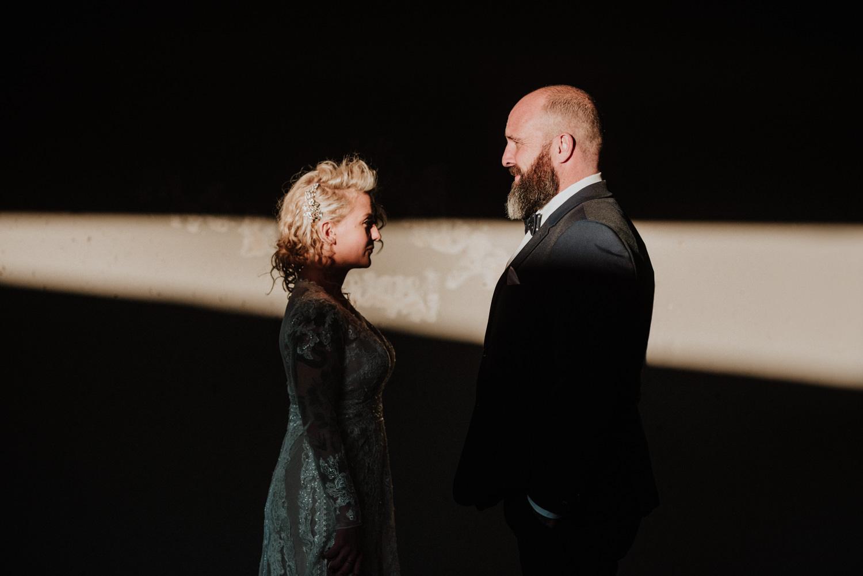 alternative bride and groom standing in beam of light in underground parkade in east vancouver